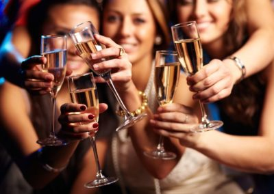 21278329 - group of partying girls clinking flutes with sparkling wine